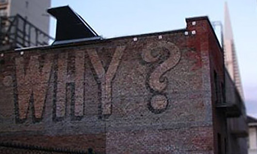 """Why?"" spray painted on the side of a brick building"