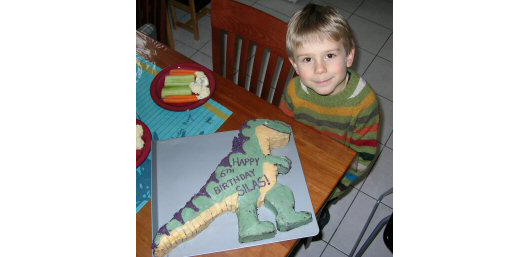 Silas beside his dinosaur birthday cake