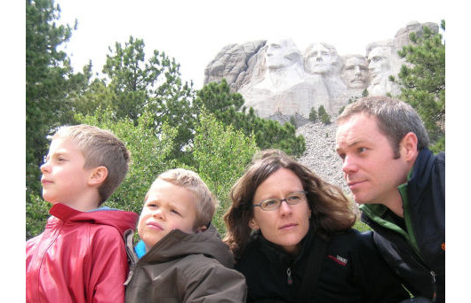 The Workman family posing in front of Mount Rushmoore