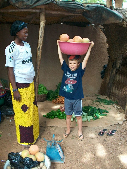 In Ouagadougou, Efrem trying to balance a bowl of fruit on his head like the fruit vendor