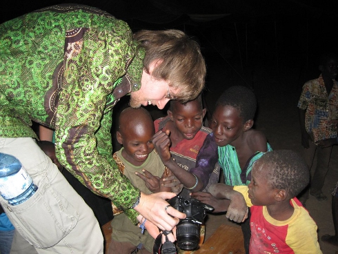 Photographer showing African boys their pictures on his digital camera.