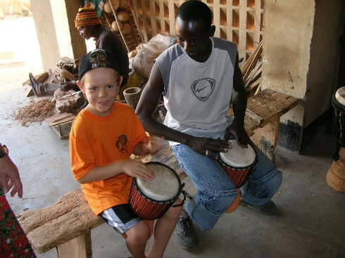 Playing a djembe beside the artisan who makes and sells them.