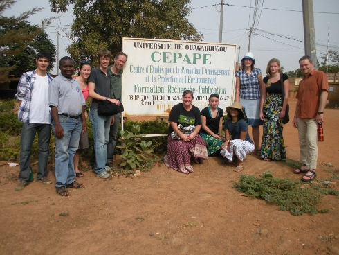 Team with national campus director posing beside a University of Ouagadougou sign